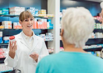 Chemist advising senior couple on a prescription drug in her pharmacy